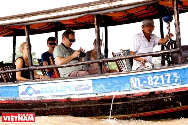 Du khách đi thuyền dọc con sông Cái Bè ngắm những khu chợ nổi.