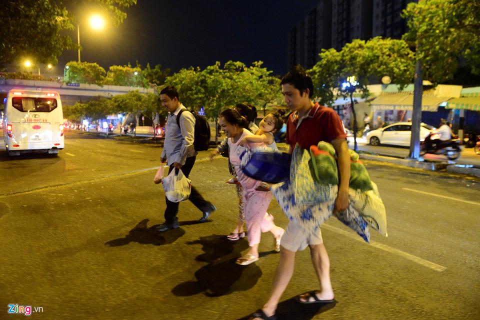 Một gia đình băng qua đường Võ Văn Kiệt để tìm đến chung cư đối diện ở tạm.