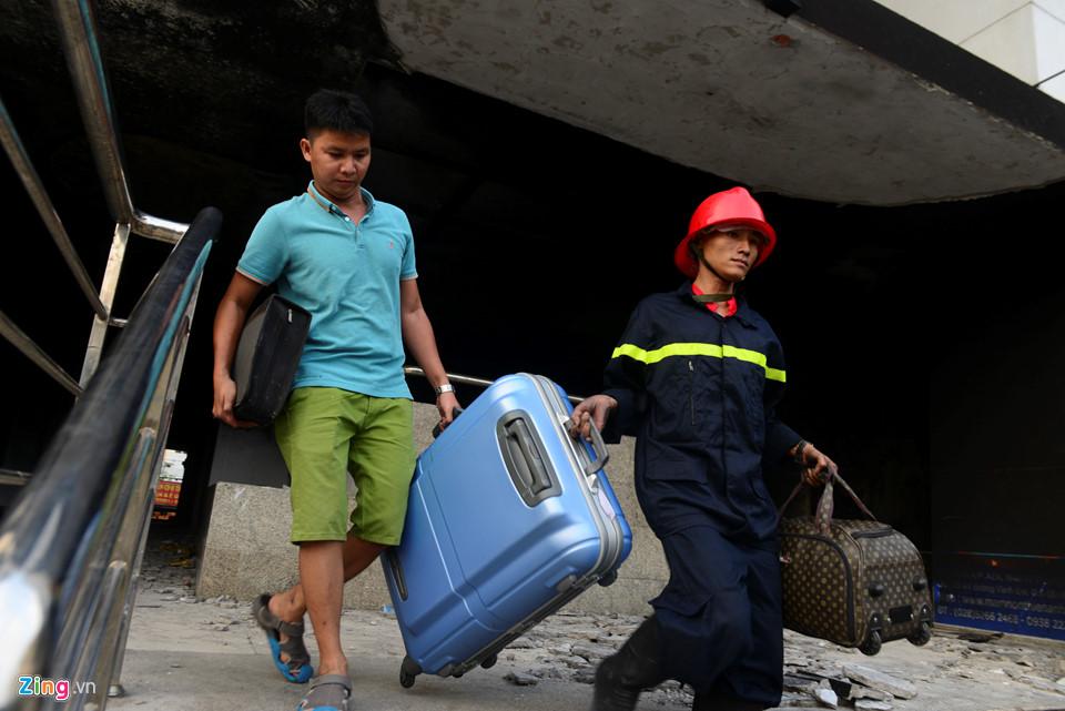 Anh Nguyễn Hữu Trực vận chuyển vali trong sự giúp sức của cảnh sát PCCC. Anh cùng gia đình qua nhà người thân đối diện đó xin ở nhờ.