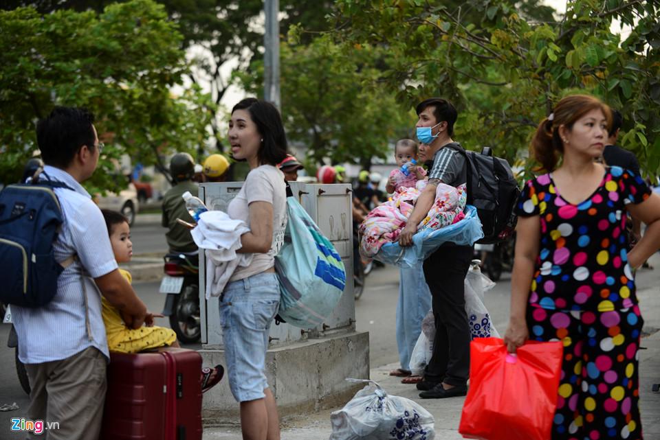 Người dân tay xách nách mang chăn, gối, quần áo... để đón xe đi tìm chỗ ở.