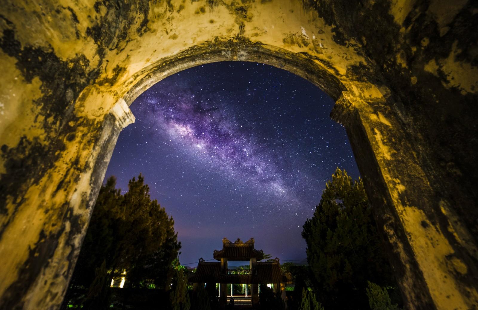 Một cánh cổng di tích cổ về đêm với dải ngân hà.