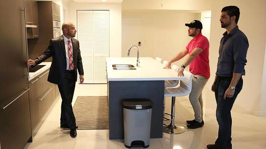 Chuyên gia môi giới (bên trái) với người mua thăm quan một ngôi nhà ở hạt Doral, bang Florida, Mỹ