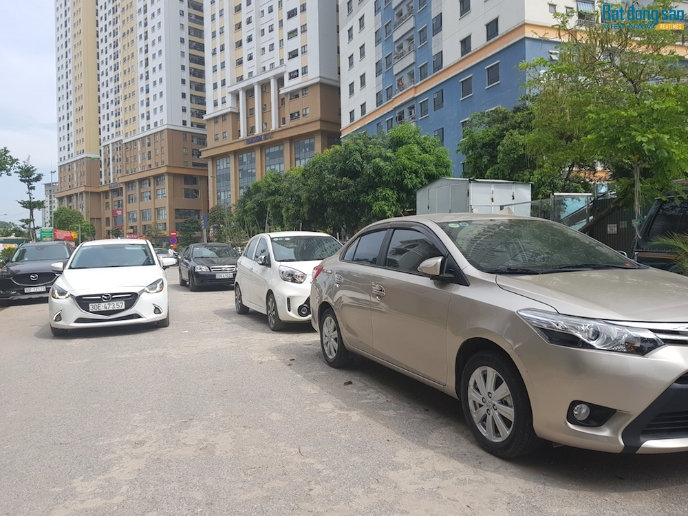 """Hàng trăm xe ô tô của cư dân khu đô thị Kim Văn - Kim Lũ bất ngờ không còn chỗ gửi xe nên phải đậu la liệt dưới lòng đường. Vào đầu giờ sáng và cuối ngày làm việc, việc """"tập kết"""" xe ô tô đã gây ra cảnh ùn ứ, lộn xộn gây mất mỹ quan đô thị. Xế hộp tràn xuống lòng đường khi bãi xe bị giải tỏa."""