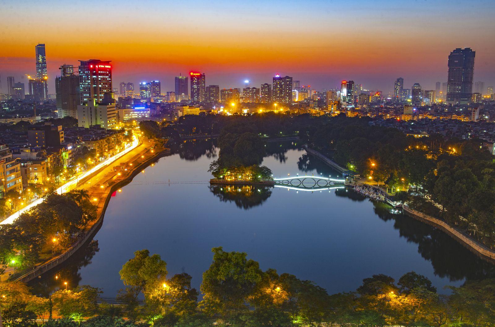 Hồ Thủ Lệ phẳng lặng như mặt gương phản chiếu ánh sáng cuối ngày, xa xa là các khu đô thị mới với những tòa nhà hiện đại