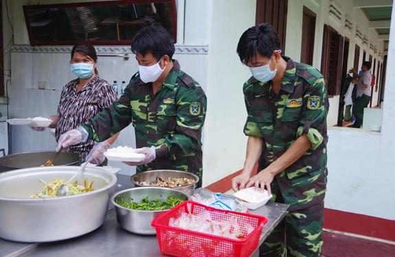 Cán bộ, chiến sĩ, nhân viên Trung đoàn 812 (Bộ CHQS tỉnh Bình Thuận) chuẩn bị bữa ăn cho người dân tại khu cách ly. Ảnh: Duy Thỉnh, Duy Hiển