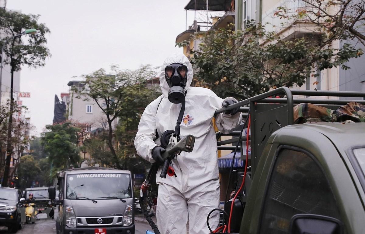 Lực lượng bộ đội hóa học triển khai phun hóa chất tiêu tẩy khu vực phố Châu Long, quận Ba Đình. Ảnh: Dương Giang/TTXVN